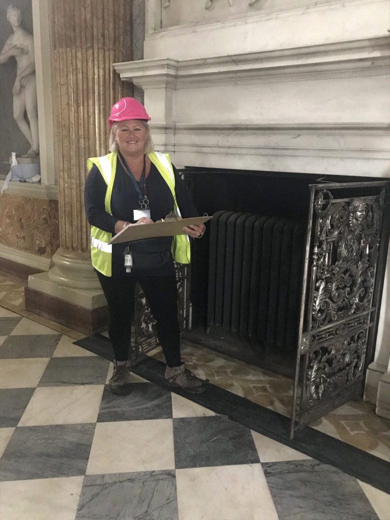 WWPT's facilities manager Julie Readman checking a radiator from 1908 in the Marble Saloon