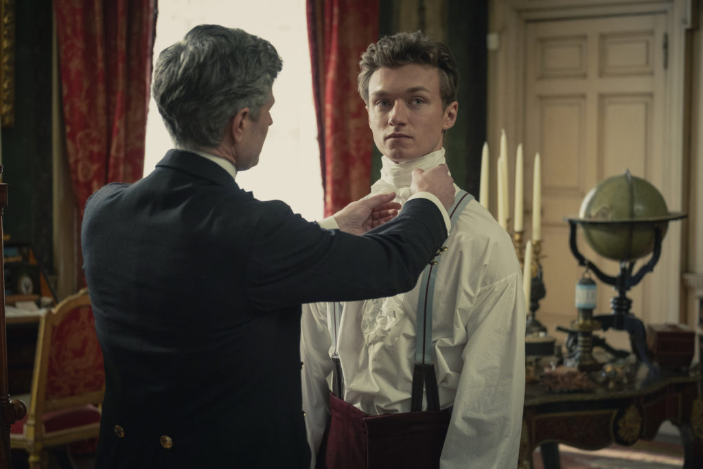 A man being helped to dress in a ruffled shirt in an opulent room.