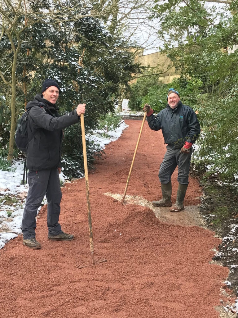 Two male volunteers holding rakes stand either side of the newly laid red path.