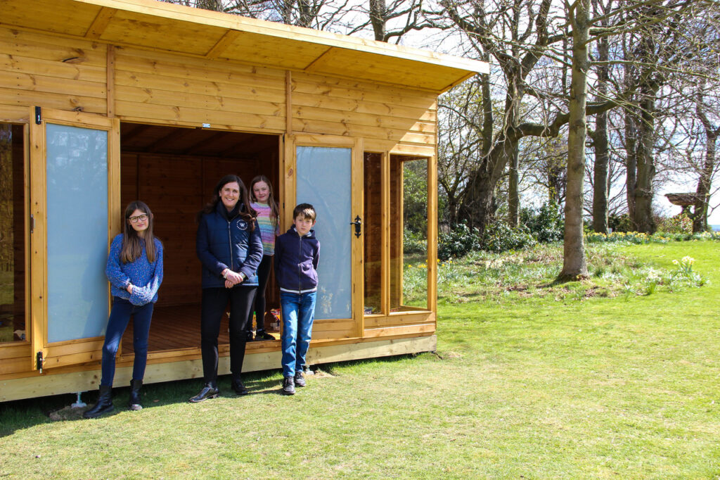 COO Paula and children in front of a wooden cabin.