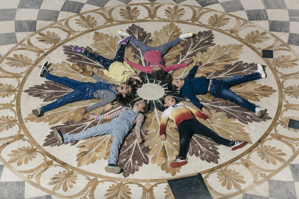 A group of children lie on the floor copying the pattern of tiles in the marble saloon.