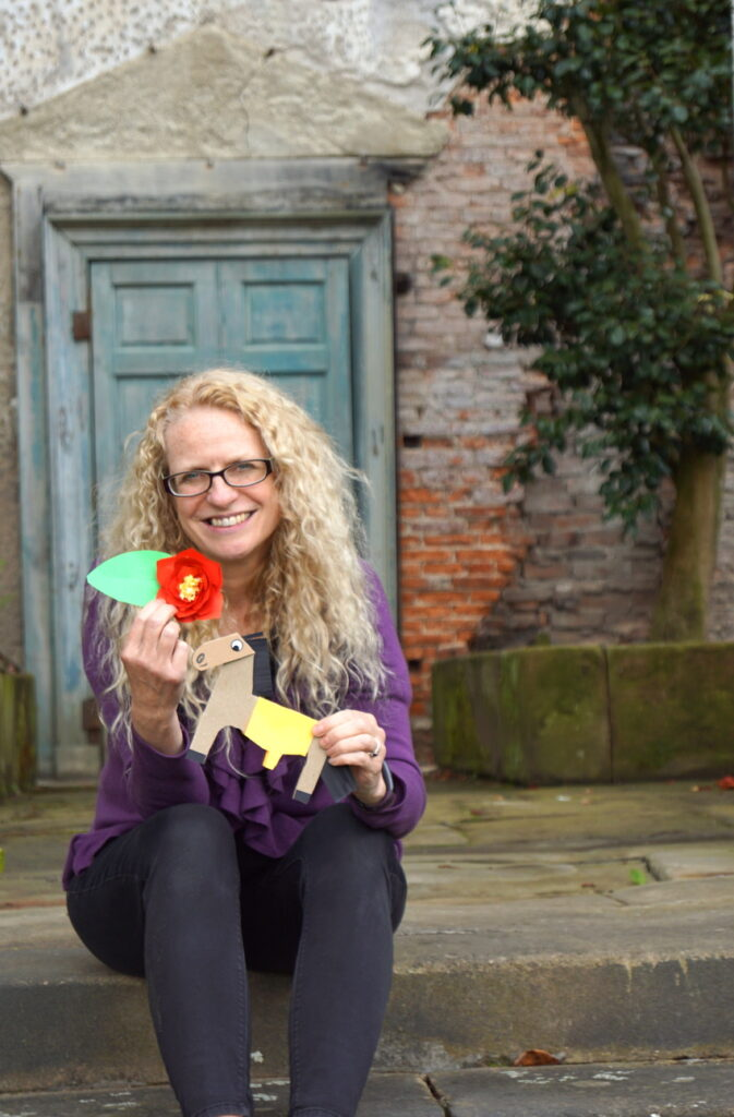 Dr Suzanne Carter sits on a step in front of an old door holding a paper camellia and horse.