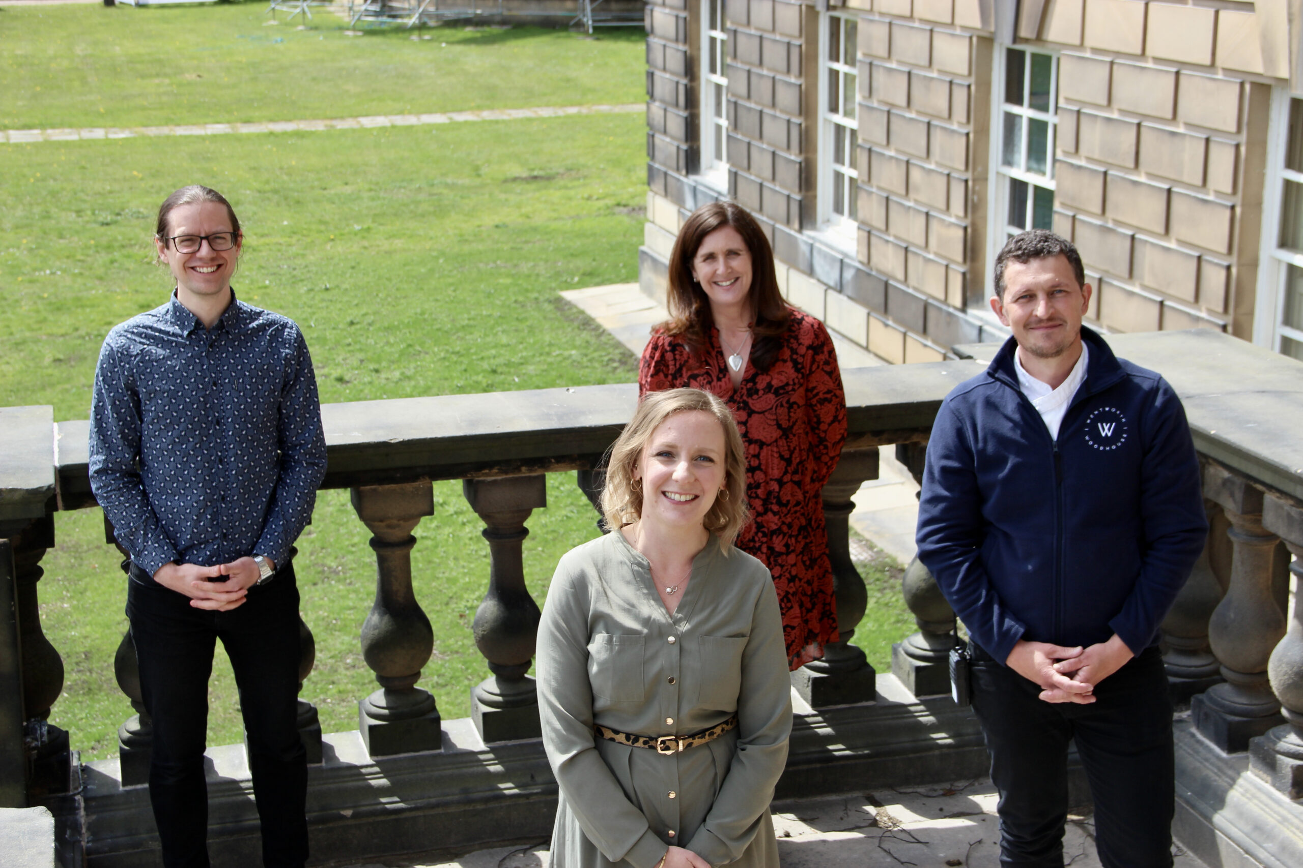 The new staff at Wentworth stand outside the building and smile at the camera.