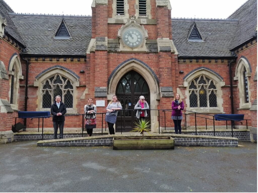 Staff stand in a socially distanced line in front of the Lye and Wollescote Chapel