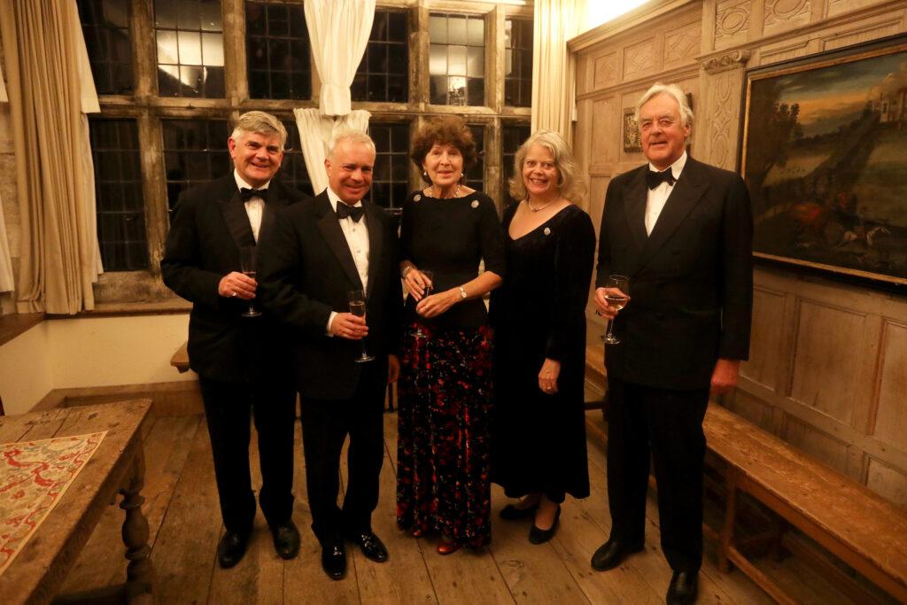 Five ladies and gentlemen in black tie stand in a line .